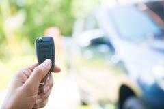 Женщина отжала на remote для того чтобы раскрыть автомобиль Стоковая Фотография RF