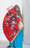 Женщина отжимает к себе большой вентилятор Стоковые Изображения RF