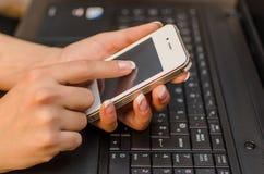 Женщина с компьтер-книжкой и телефоном Стоковое Фото