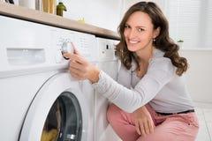 Женщина отжимая кнопку стиральной машины стоковые фотографии rf