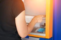 Женщина отжимая номер пароля на голубой машине ATM Стоковое Изображение