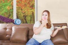 Женщина отказывает гантель и ест donuts Стоковые Изображения