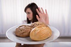 Женщина отказывая плиту хлеба и печений стоковое фото