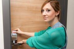 Женщина открывая дверь Стоковые Изображения