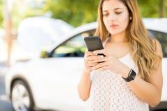 Женщина отправляя СМС для помощи автомобиля стоковое изображение rf