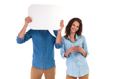 Женщина отправляя СМС пока человек покрывает его сторону с пузырем речи Стоковая Фотография