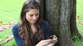 Женщина отправляя СМС в парке акции видеоматериалы