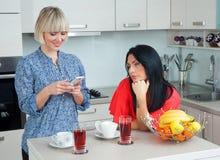Женщина отправляя СМС на мобильном телефоне в компании Стоковое Фото