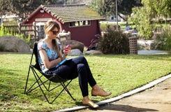Женщина отправляя СМС на парке Стоковые Фотографии RF