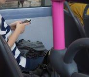 Женщина отправляя СМС на шине Стоковое Изображение