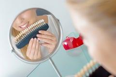 Женщина отражения Miror держа зубы красит образцы против рта Стоковые Изображения RF