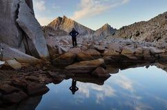 Женщина отраженная в озере гор стоковое изображение