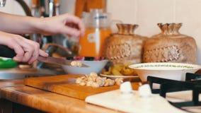 Женщина отрезает грибы в кухне акции видеоматериалы