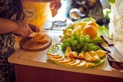 Женщина отрезала апельсины стоковое изображение