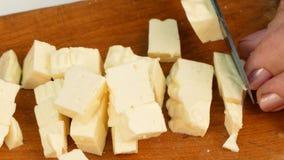 Женщина отрезала сыр с ножом видеоматериал
