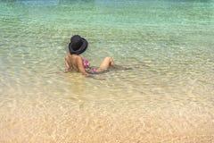 Женщина от за носить шляпу лежа в воде на крае песчаного пляжа в Окинава, Японии стоковые изображения rf