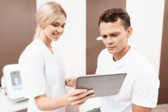 Женщина от салона красоты показывает данные по человека на процедурах в его серой таблетке стоковое изображение