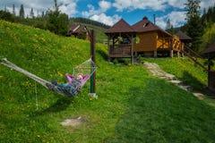 Женщина отдыхая в гамаке в горах деревянные дома на предпосылке и зеленой траве Стоковое фото RF