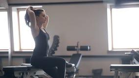 Женщина отдыхая после разминки на тренерах внутри спортзала видеоматериал