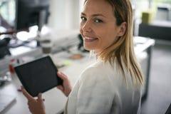 женщина офиса дела Женщина используя цифровую таблетку и смотреть Стоковая Фотография