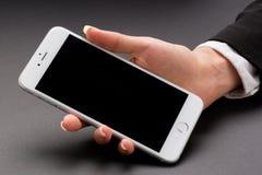 Женщина офиса держит белый smartphone Стоковое Фото