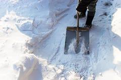 Женщина очищает путь от снега с лопаткоулавливателем металла Чистка снега Стоковое Фото