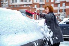Женщина очищает снег от автомобиля Стоковые Изображения