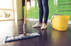 Женщина очищая ее кухню Стоковая Фотография