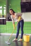 Женщина очищая ее кухню Стоковые Фото