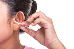 Женщина очищая ее ухо путем использование ручки бутона хлопка изолированной на whi Стоковое Изображение RF