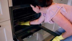 Женщина очищая печь видеоматериал