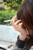 женщина ощупывания усиленная курильщицей Стоковые Фото