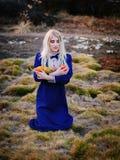 Женщина одела в голубом винтажном платье сидит в парке осени стоковое фото rf
