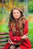 Женщина одела в красном пальто сидя в парке осени Стоковая Фотография