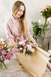 Женщина пакуя розовое взгляд сверху букета весны Стоковые Фотографии RF