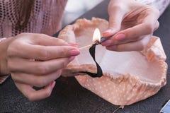 Женщина палит край ленты осветила спичку Руки конца-вверх стоковые фото