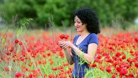 Женщина пахнет цветками в поле сток-видео