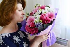 Женщина пахнуть букетом цветков Стоковое Изображение RF