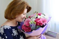 Женщина пахнуть букетом цветков Стоковые Фото