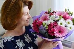 Женщина пахнуть букетом цветков Стоковая Фотография