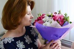 Женщина пахнуть букетом цветков Стоковые Фотографии RF