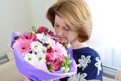 Женщина пахнуть букетом цветков Стоковые Изображения