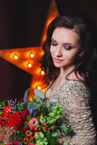 Женщина певицы в платье яркого блеска с звездой Бродвей на предпосылке Курчавый стиль причёсок, совершенный состав Цветки в ее ру Стоковая Фотография