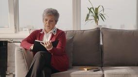 Женщина пенсионера сидя на кресле и писать рассказ на книге сток-видео