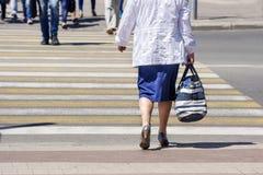Женщина пересекая улицу в городе Стоковые Фото