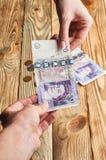 Женщина передает фунт стерлинга к человеку Стоковая Фотография RF