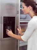 Женщина перед холодильником aa Стоковые Фотографии RF