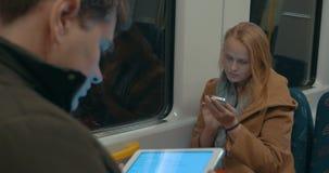 Женщина печатая в Smartphone пока едущ метро сток-видео