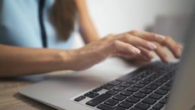 Женщина печатая на клавиатуре ноутбука в офисе Конец вверх по рукам женщины писать на клавиатуре ноутбука видеоматериал