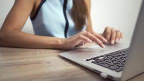Женщина печатая на клавиатуре ноутбука в офисе Конец вверх по рукам женщины писать на клавиатуре ноутбука акции видеоматериалы